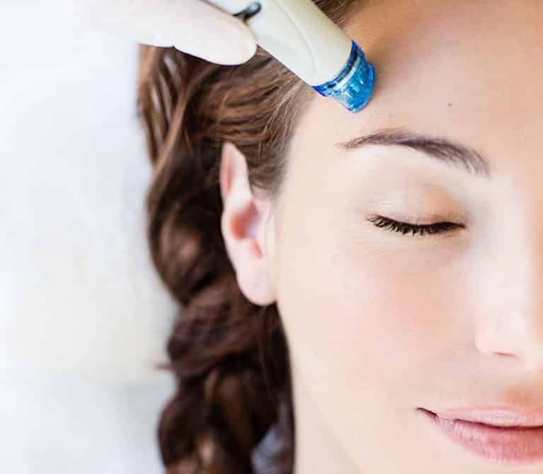 Woman receiving a HydraFacial treatment.
