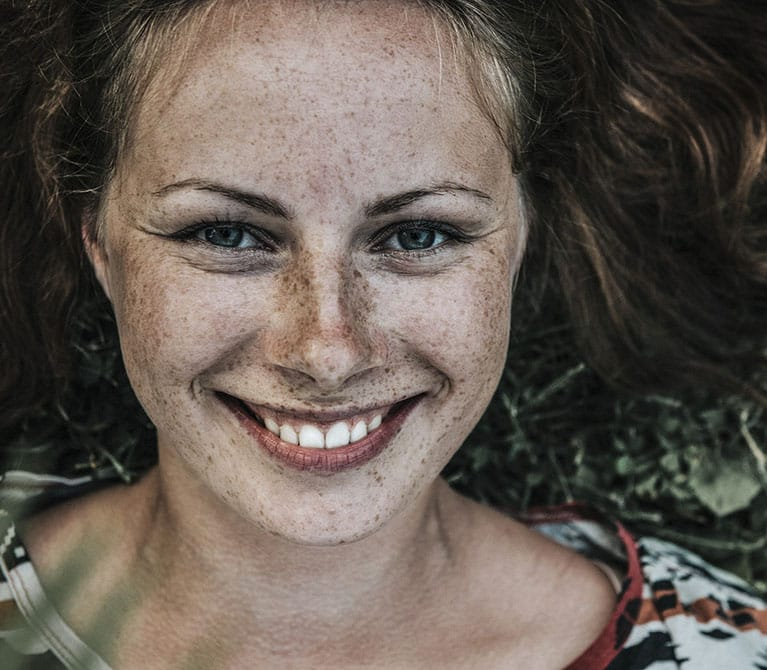 Woman with freckles all over her face lying down on her back and smiling directly into the camera.