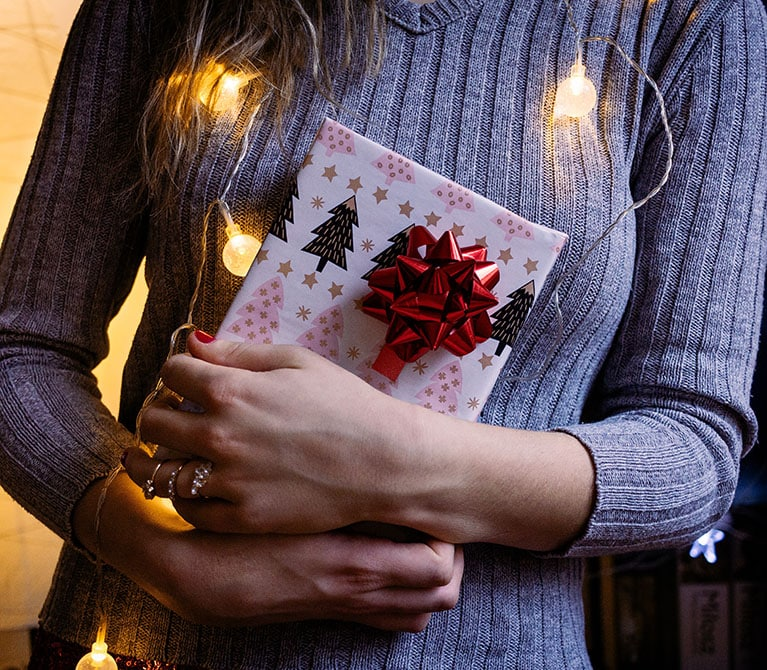 Woman holding a wrapped gift in front of a