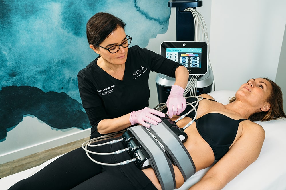 Med spa esthetician setting up an InMode Evolve Trim body contouring treatment for the abdomen for a spa guest.