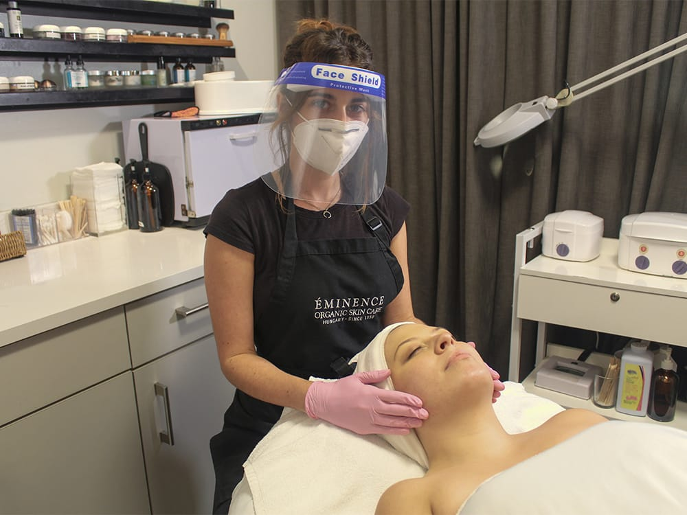 Aesthetician wearing a mask and face shield during a facial treatment with a client.