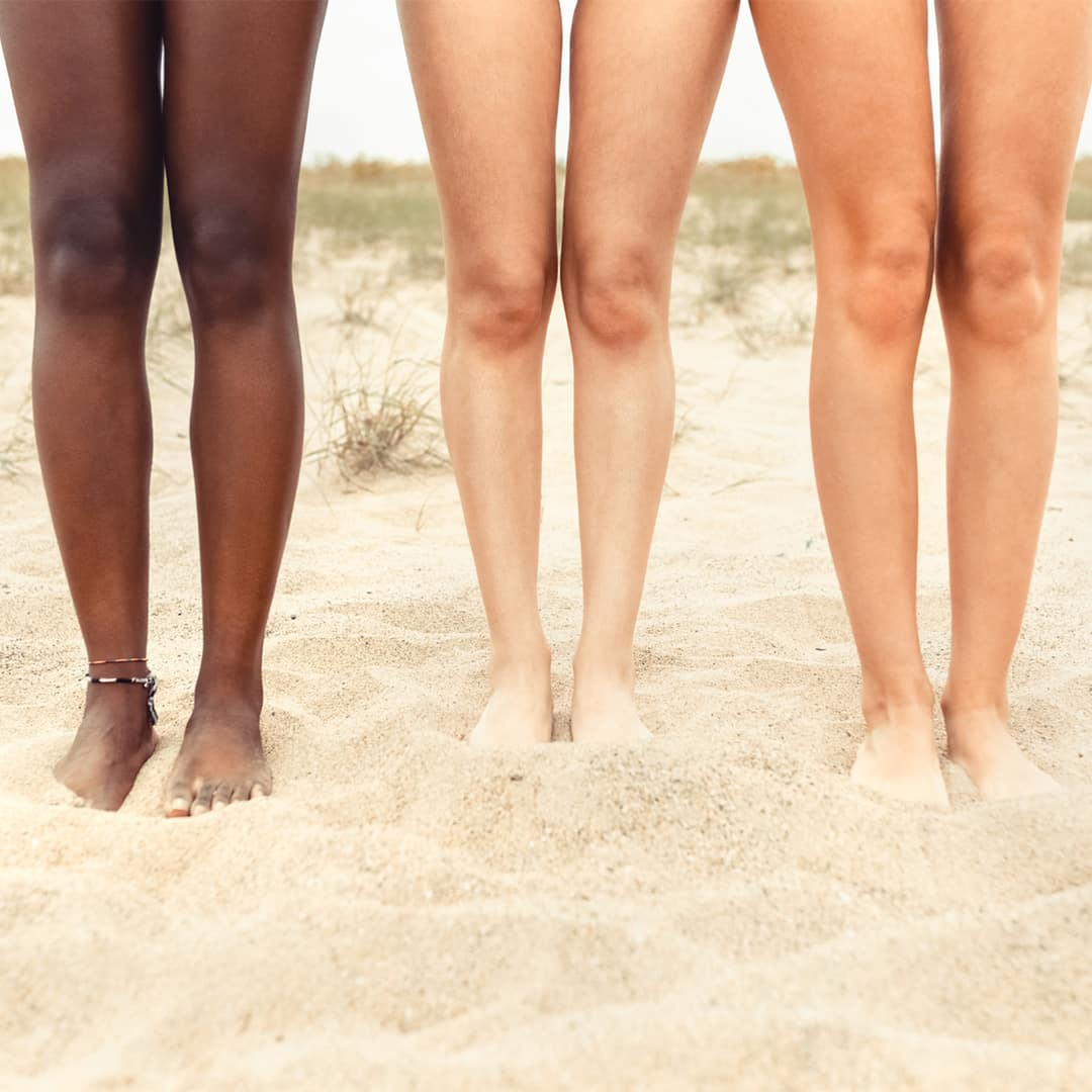 Image of three woman's legs with different skin tones standing on a beach.