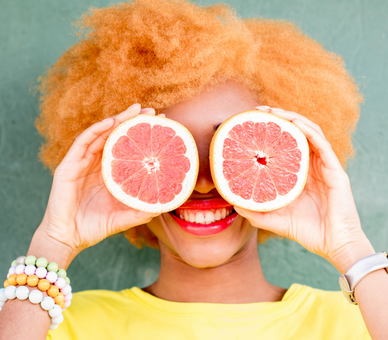 Close-up of smiling woman holding two grapefruit halves in front of her eyes.
