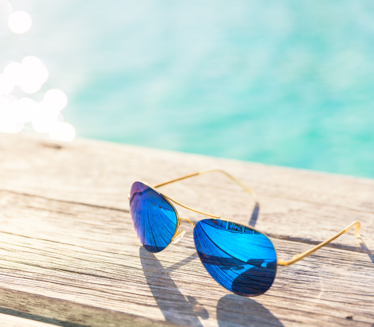 Pair of aviator sunglasses sitting on a wooden dock with sunshine reflecting off the water behind them.