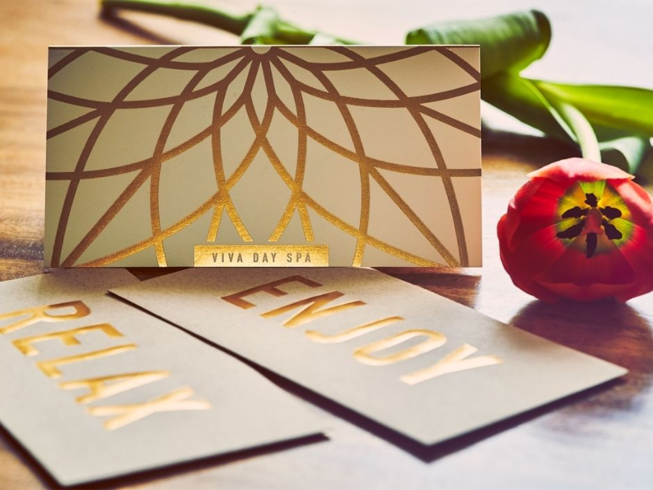 """Classic gold foil Viva Day Spa gift certificate on a wood table, with envelopes options that read """"Relax"""" and """"Enjoy"""""""