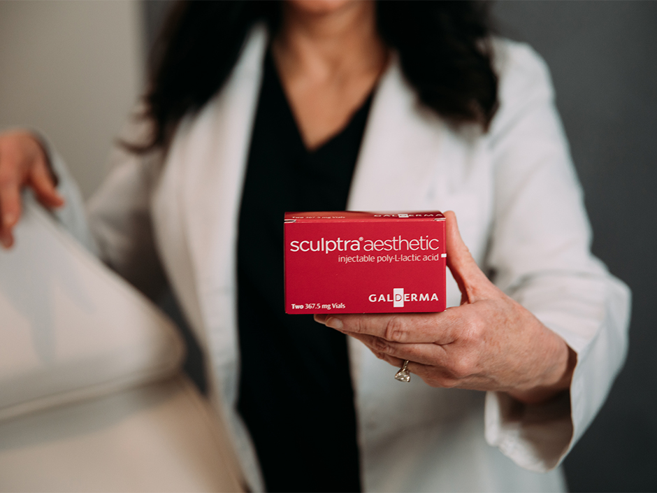 Nurse Practitioner cosmetic injector holding a box of Sculptra Aesthetic dermal filler.